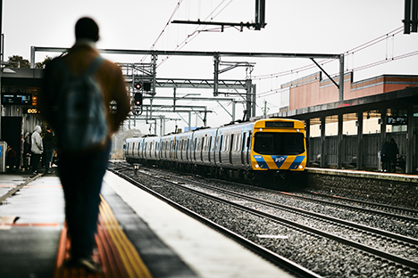 Image shows a person walking on a station platform in the foreground. In the background is a train on the Sunbury line as it pulls into a station.