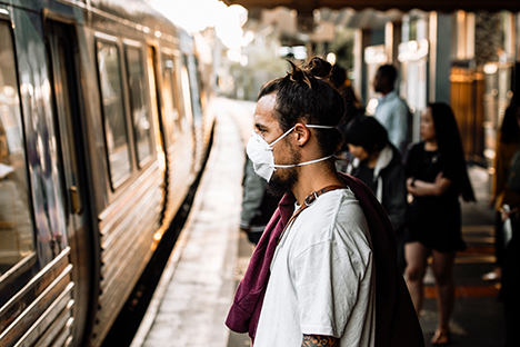 Image shows a man standing on a train platform wearing a face mask during the COVID-19 pandemic while waiting for a train.