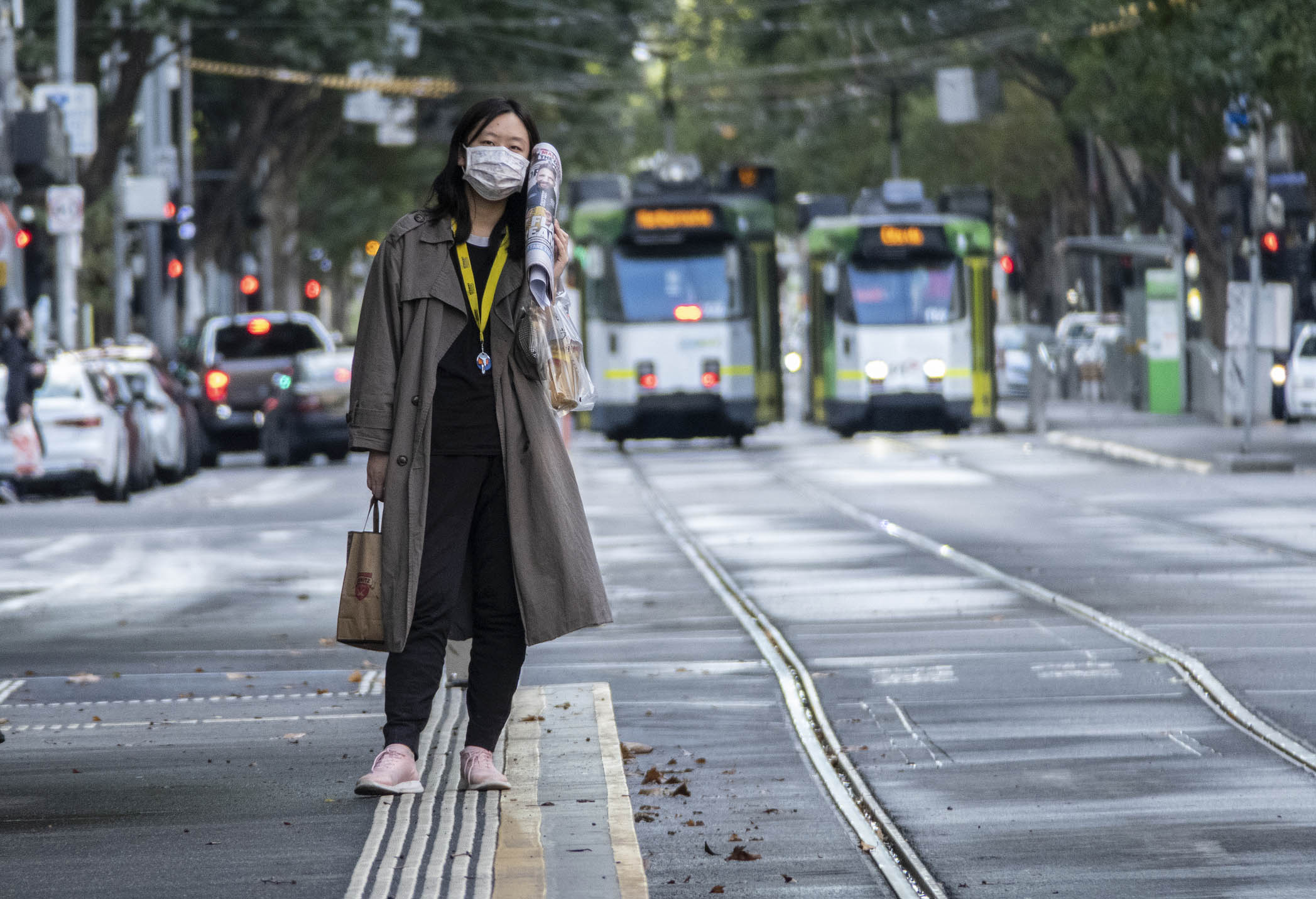 Image shows a person wearing a face mask while waiting at a tram stop during the COVID-19 pandemic.