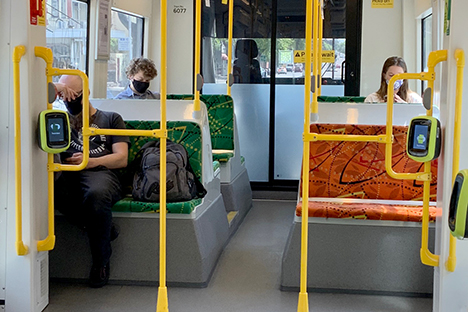 Image shows three people wearing face masks and employing social distancing while travelling on a tram.