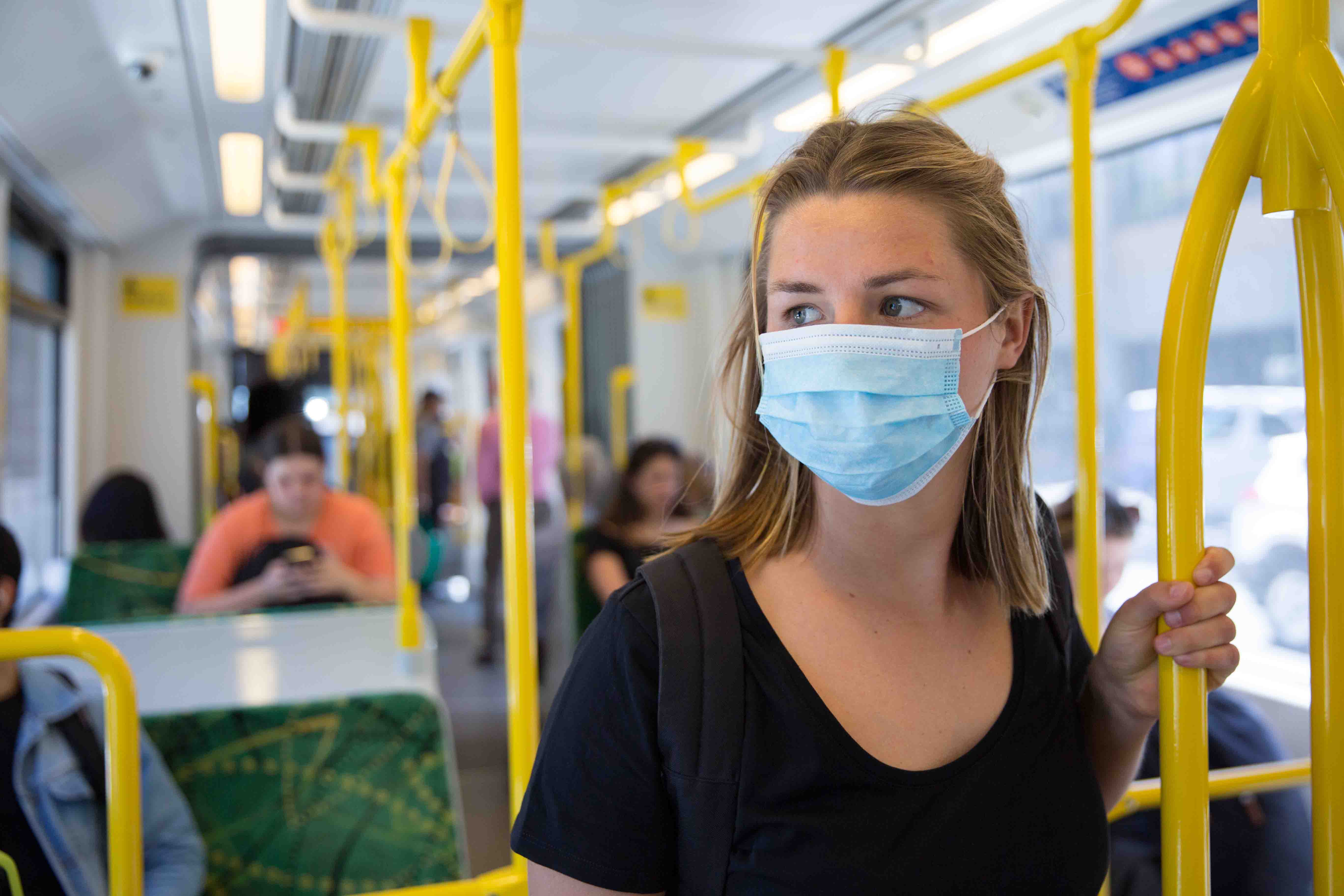 Image shows a woman on a tram wearing a surgical face mask during the COVID-19 pandemic.