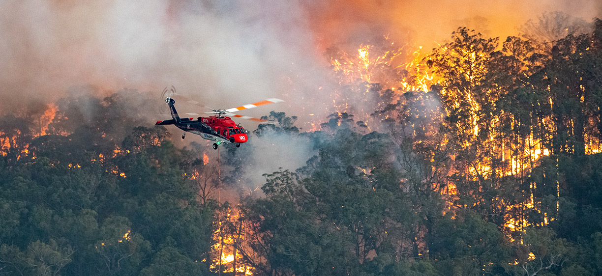 Photograph shows a firefighting helicopter at the Mallacoota fire.